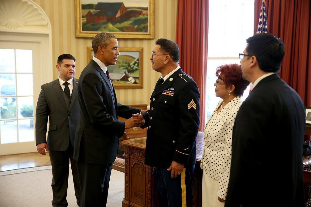 . President Barack Obama speaks with U.S. Army Specialist Four (Ret.) Santiago J. Erevia, a Vietnam War veteran, in the Oval office before presenting him with the Medal of Honor at a ceremony in the White House on March 18, 2014 in Washington, DC.  Erevia, U.S. Army Staff Sgt. (Ret.) Melvin Morris, and U.S. Army Sgt. First Class (Ret.) Jose Rodela were joined by families of 21 others who were presented posthumously with the Medal of Honor for conspicuous gallantry.   (Photo by Joe Raedle/Getty Images)