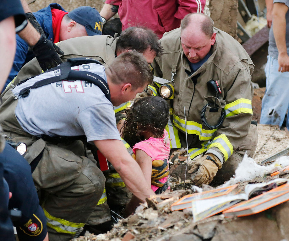 . A child is pulled from beneath a collapsed wall at the Plaza Towers Elementary School in following a tornado in Moore, Okla., Monday, May 20, 2013. (AP Photo Sue Ogrocki)