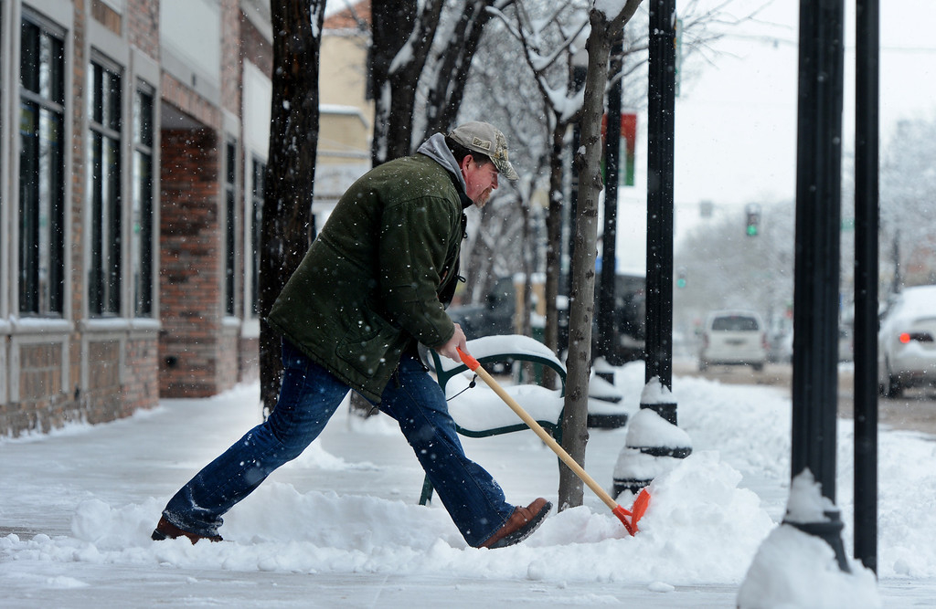. Building Manager Michael Dodge shovels the sidewalk outside the Main Street Apartments in Littleton, CO February  21, 2013. The Friday forecast calls for mostly cloudy skies and highs near 40. (Photo By Craig F. Walker/The Denver Post)