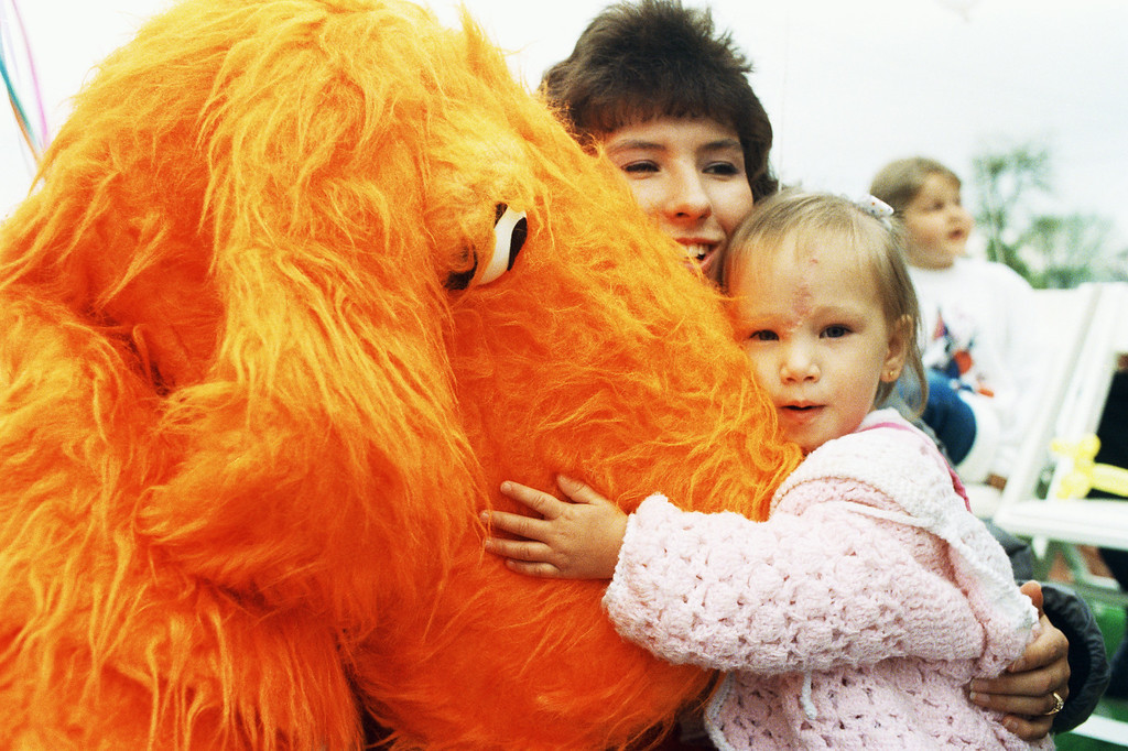 . Two-year-old Jessica McClure hugs a dog character during a fund raiser in Lancaster, Texas on Thursday, March 31, 1988, for a young boy in need of a heart-lung transplant. Jessica attracted international attention in October when she was trapped for more than 50 hours in a dry well in Midland, Texas. Her mother Reba is in the background. (AP Photo/Ron Heflin)