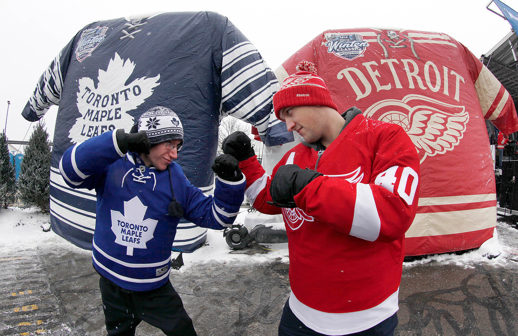 . Nathan Dunville, of Halifax, Nova Scotia, left, and Adam Boutilier, of Cole Harbour, Nova Scotia, pose for family photographs at the NHL Winter Classic hockey game at Michigan Stadium in Ann Arbor, Mich., Wednesday, Jan, 1. 2014, where the Detroit Red Wings play the Toronto Maple Leafs. (AP Photo/Paul Sancya)