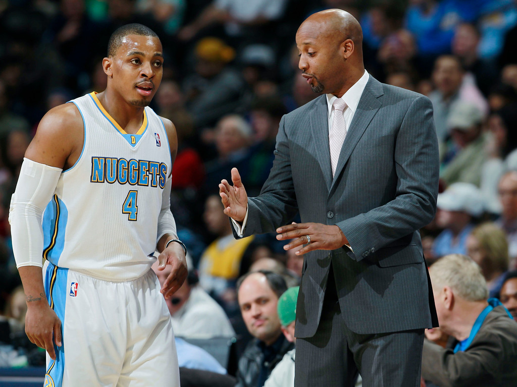 . Denver Nuggets head coach Brian Shaw, right, confers with guard Randy Foye during a break against the Utah Jazz in the first quarter of an NBA basketball game in Denver on Friday, Dec. 13, 2013. (AP Photo/David Zalubowski)
