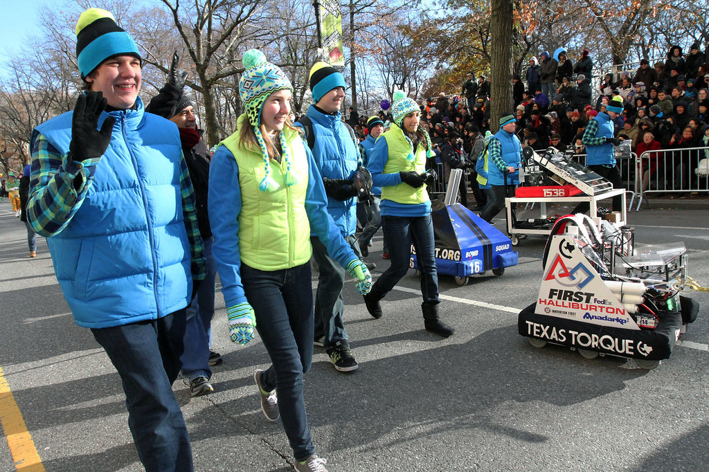 . Members of the Texas Torque robotics team, foreground from left, Josh Beridon, 17, Caroline Wageman, 16, Robert Oakley, 18, and Vaishu Kishore, 17, march with Sonic, the Texas Torque robot, right, during the Macy\'s Thanksgiving Day Parade Thursday Nov. 28, 2013 in New York. (AP/Tina Fineberg)