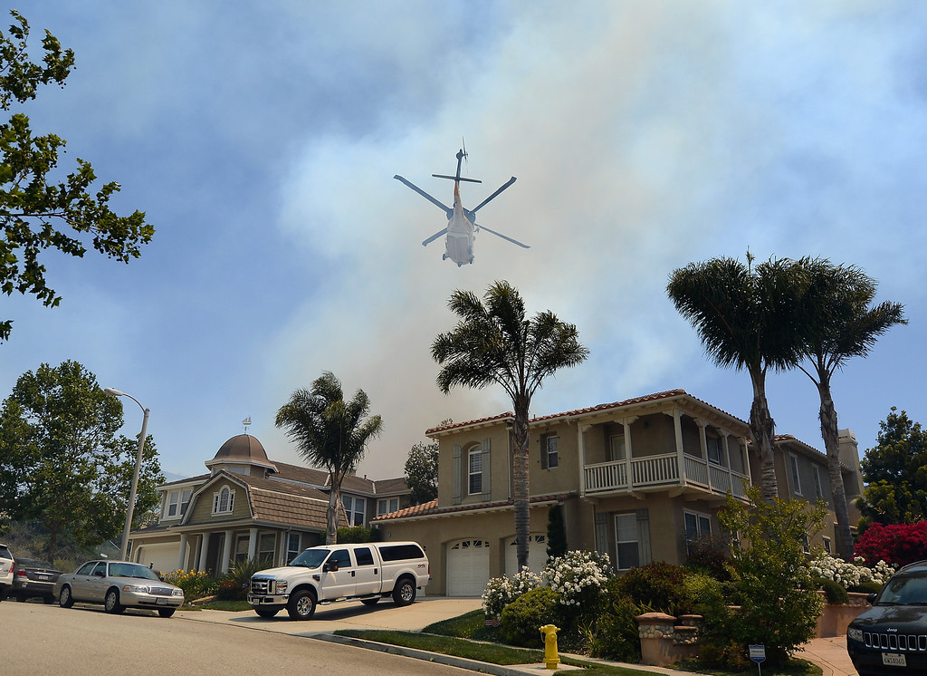 . A fire fighting helicopter comes in to make a water drop behind some home threatened by a wildfire on May 2, 2013 in Newbury Park, California.   (Photo by Kevork Djansezian/Getty Images)