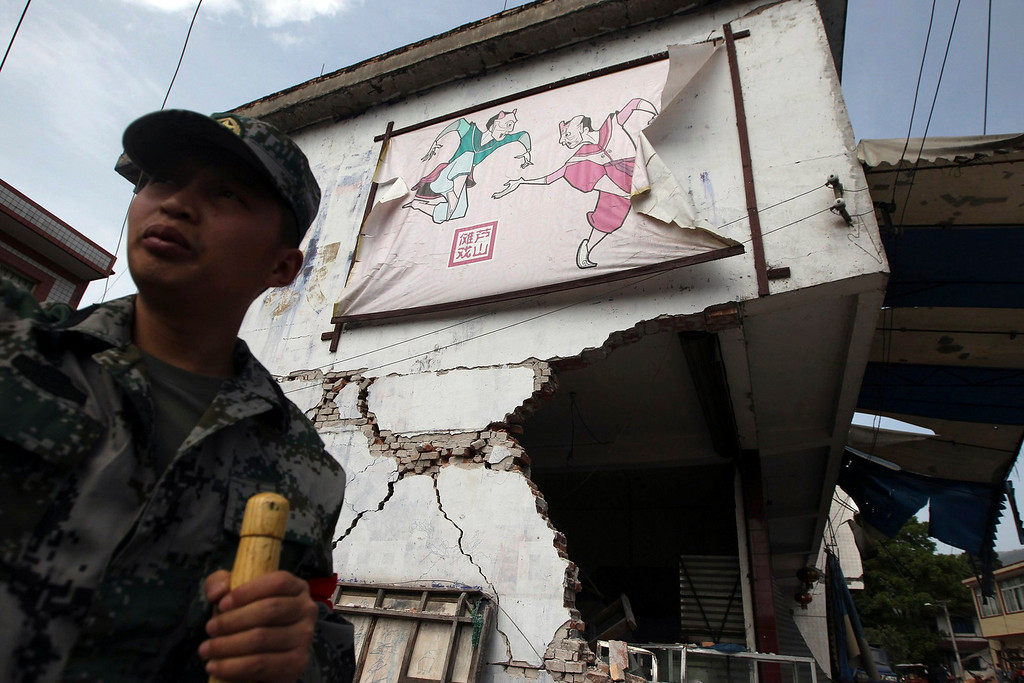 . A rescue worker stands in front of damaged houses after a strong 6.6 magnitude earthquake, at Longmen village, Lushan county, Ya\'an, Sichuan province April 20, 2013. The earthquake hit a remote, mostly rural and mountainous area of southwestern China\'s Sichuan province on Saturday, killing at least 102 people and injuring about 2,200 close to where a big quake killed almost 70,000 people in 2008.     REUTERS/Stringer