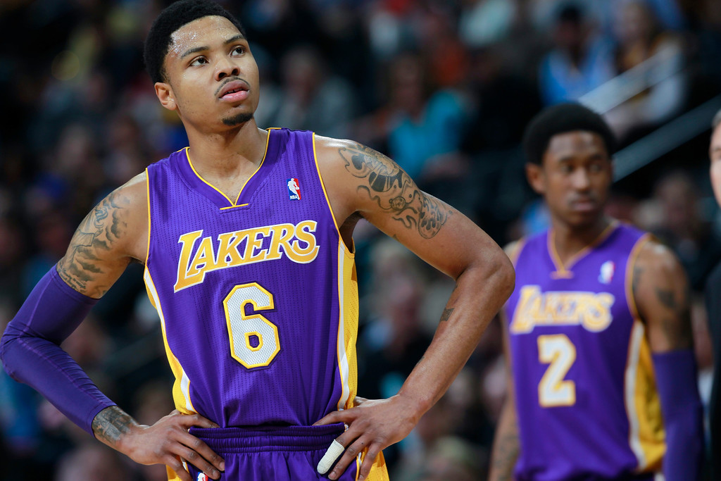 . Los Angeles Lakers guard Kent Bazemore, front, looks on against the Denver Nuggets as guard MarShon Brooks, back, checks in to play in the first quarter of an NBA basketball game in Denver on Friday, March 7, 2014. (AP Photo/David Zalubowski)