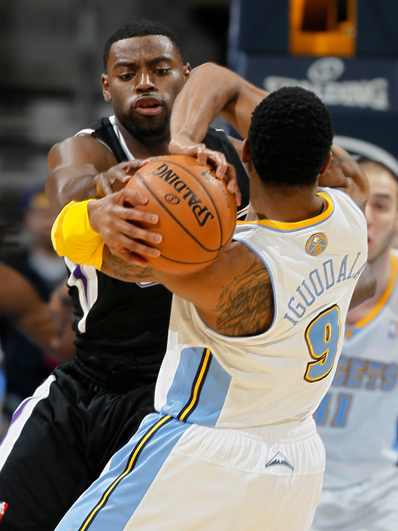. Sacramento Kings guard Tyreke Evans, left, tries to steal the ball from Denver Nuggets guard Andre Iguodala during the first quarter of an NBA basketball game in Denver on Saturday, Jan. 26, 2013. (AP Photo/David Zalubowski)