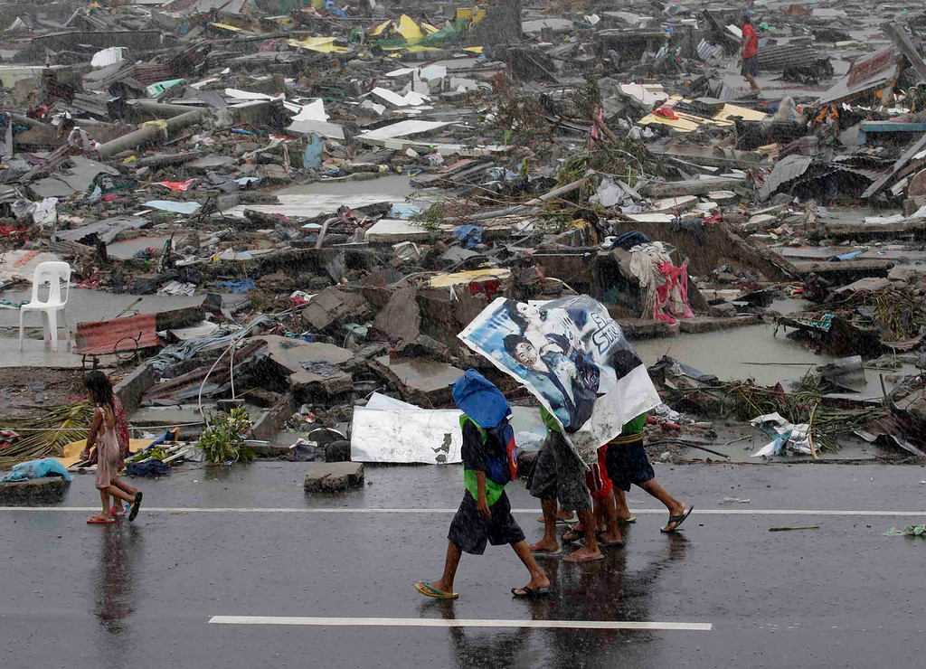 . Residents use a tarpaulin to shield them from rain in typhoon struck Tacloban city, Leyte province central Philippines on Sunday, Nov. 10, 2013. The city remains littered with debris from damaged homes as many complain of shortage of food, water and no electricity since the Typhoon Haiyan slammed into their province.  Typhoon Haiyan, one of the strongest storms on record, slammed into six central Philippine provinces Friday leaving a wide swath of destruction and hundreds of people dead. (AP Photo/Bullit Marquez)