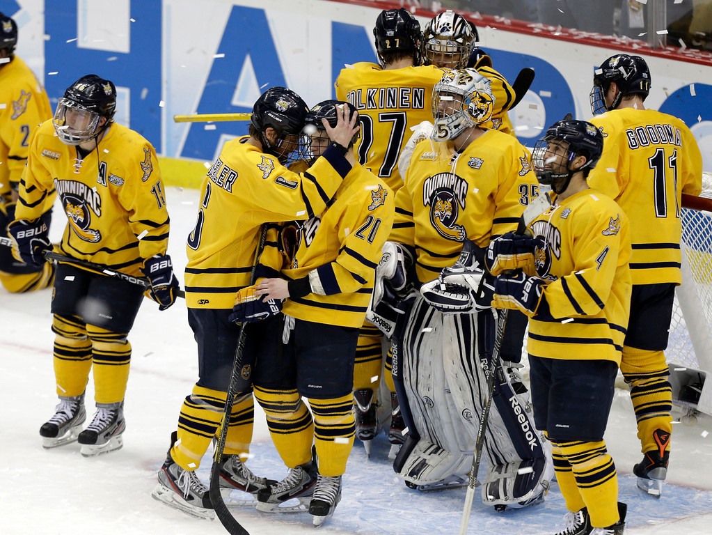 . The Quinnipiac men\'s hockey team gather around goalie Eric Hartzell, top rear right, after losing to Yale 4-0 in the NCAA men\'s college hockey national championship game in Pittsburgh Saturday, April 13, 2013. (AP Photo/Gene Puskar)