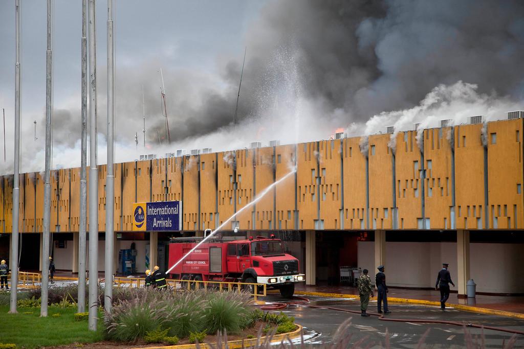 . Firefighters try to extinguish fire at the international arrivals unit of Jomo Kenyatta International Airport, Nairobi, Kenya, Wednesday, Aug. 7, 2013. (AP Photo/Sayyid Azim)