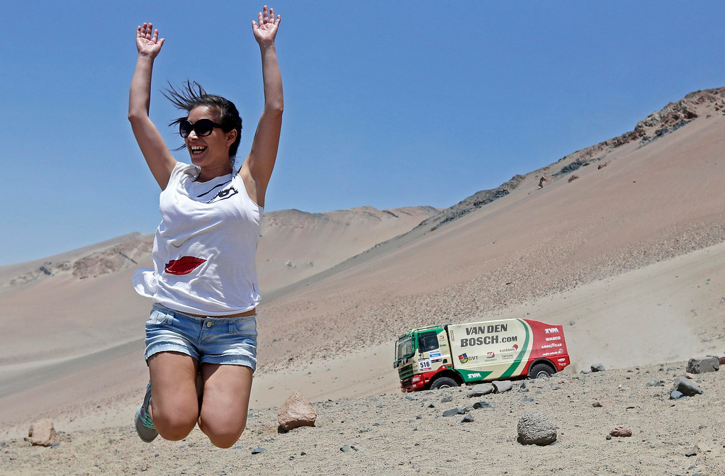 . A woman jumps as France\'s Ronan Chabot and co-pilot Gilles Pillot compete with their SMG during the 3rd stage of the Dakar Rally 2013 from Pisco to Nazca January 7, 2013.  REUTERS/Jacky Naegelen
