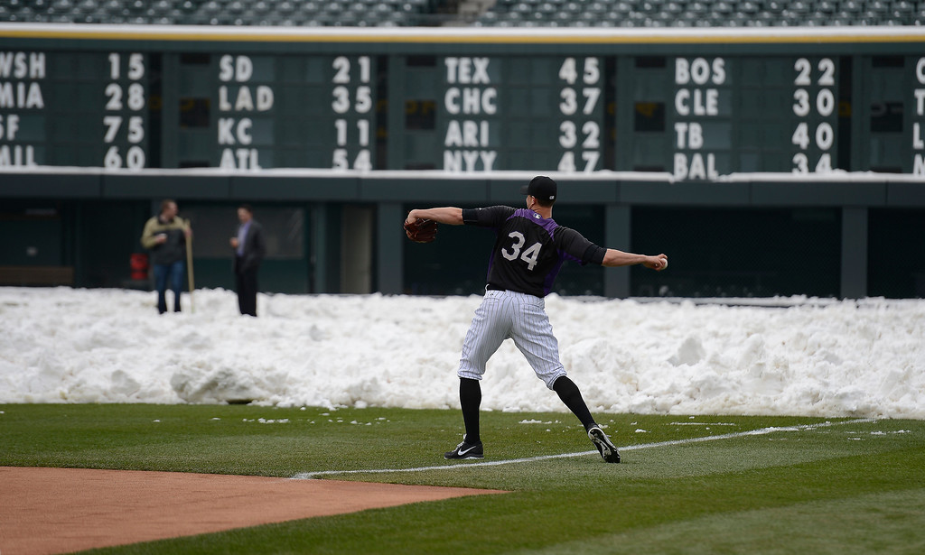 . Matt Belisle (34) of the Colorado Rockies warms up with the pile of snow in right field as a backdrop. Rockies grounds crew and employees work to clear the field of snow to get the first game of a double header in against the  New York Mets April 16, 2013 at Coors Field. (Photo By John Leyba/The Denver Post)