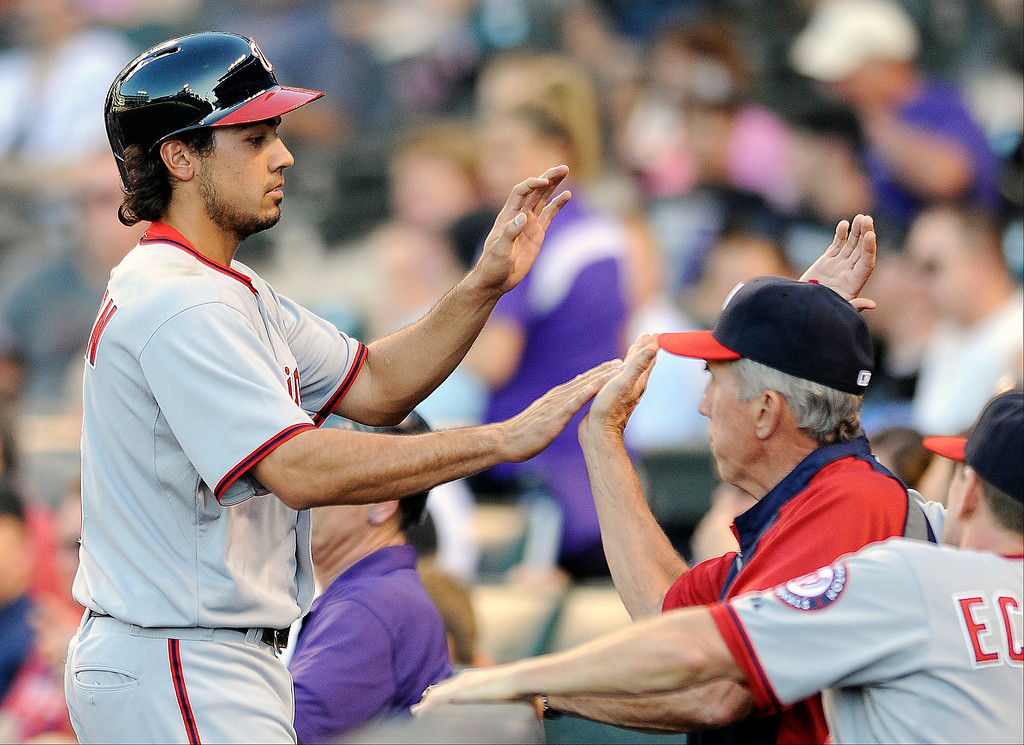 . Washington Nationals Anthony Rendon is congratulated by teammates after scoring on a two-RBI double by Denard Span in the second inning of a baseball game against the Colorado Rockies on Tuesday, June 11, 2013 in Denver. (AP Photo/Chris Schneider)