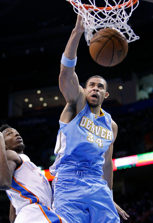. Denver Nuggets center JaVale McGee, right, dunks the ball in front of Oklahoma City Thunder\'s Hasheem Thabeet, left, during the first quarter of an NBA basketball game in Oklahoma City, Wednesday, Jan. 16, 2013.  (AP Photo/Alonzo Adams)