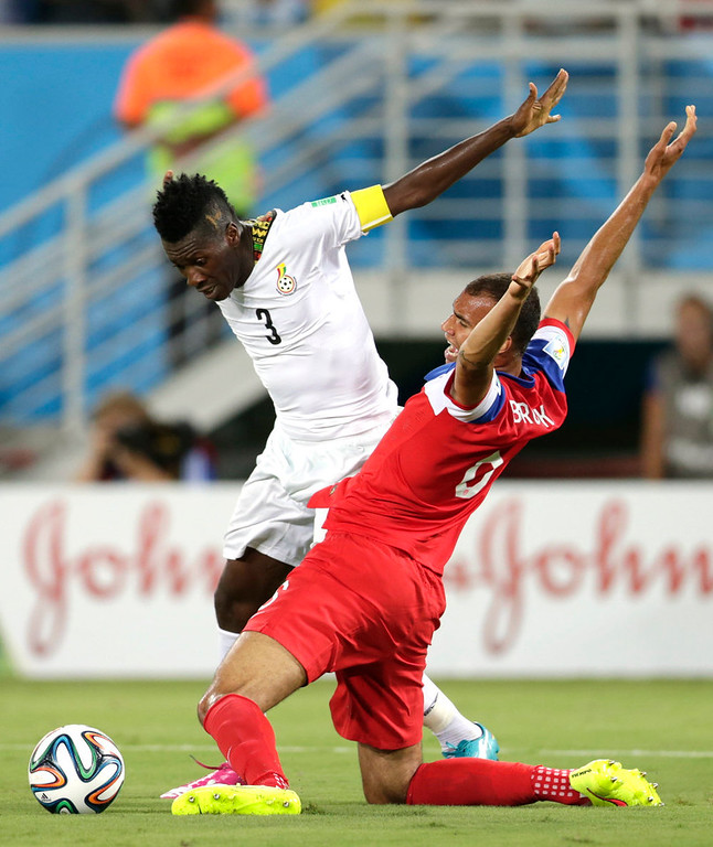 . Ghana\'s Asamoah Gyan, left, tries to get past United States\' John Brooks during the group G World Cup soccer match between Ghana and the United States at the Arena das Dunas in Natal, Brazil, Monday, June 16, 2014. (AP Photo/Dolores Ochoa)