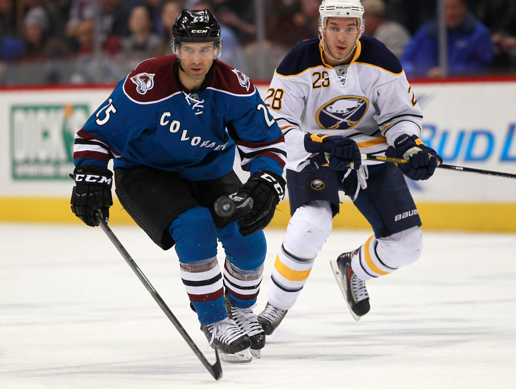 . Colorado Avalanche center Maxime Talbot, left, pursues the puck with Buffalo Sabres center Zemgus Girgensons, right, in the first period of an NHL hockey game in Denver, Saturday, Feb. 1, 2014. (AP Photo/David Zalubowski)