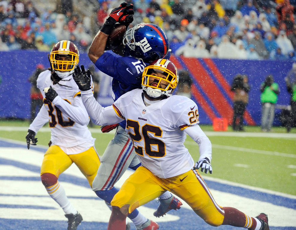 . New York Giants wide receiver Jerrel Jernigan (12) catches a pass for a touchdown in front of Washington Redskins\' Josh Wilson (26) and E.J. Biggers (30) during the first half of an NFL football game on Sunday, Dec. 29, 2013, in East Rutherford, N.J. (AP Photo/Bill Kostroun)