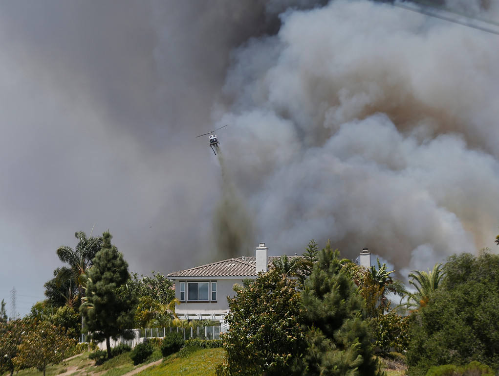 . A helicopter drops fire fighting material over a house as smoke envelopes the area  Wednesday, May 14, 2014, in Carlsbad, Calif.  Weather conditions that at least temporarily calmed allowed firefighters to gain ground early Wednesday on a pair of wildfires that forced thousands of residents to leave their homes. (AP Photo)