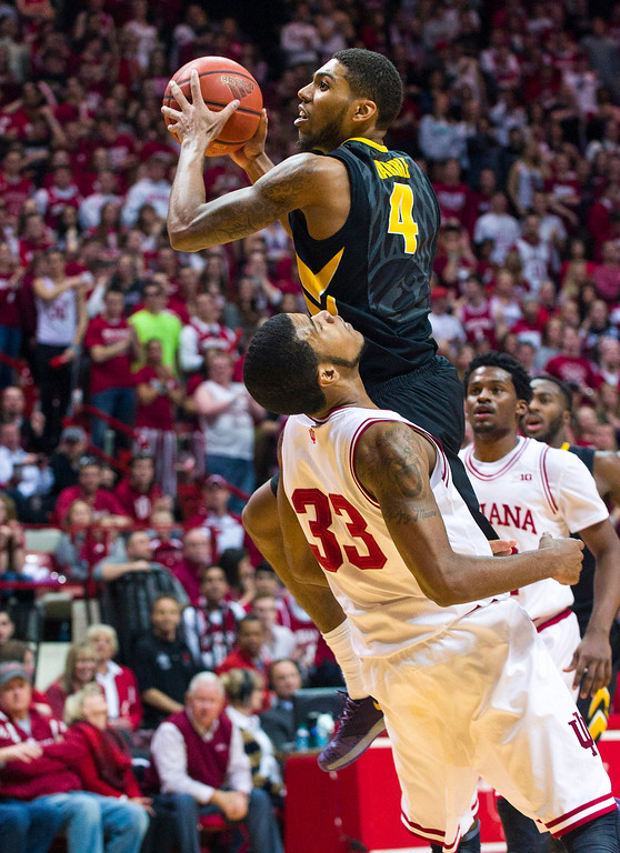 . Iowa\'s Roy Devyn Marble (4) makes contact with Indiana\'s Jeremy Hollowell (33) while driving toward the basket in the first half of an NCAA college basketball game on Thursday, Feb. 27, 2014, in Bloomington, Ind. (AP Photo/Doug McSchooler)
