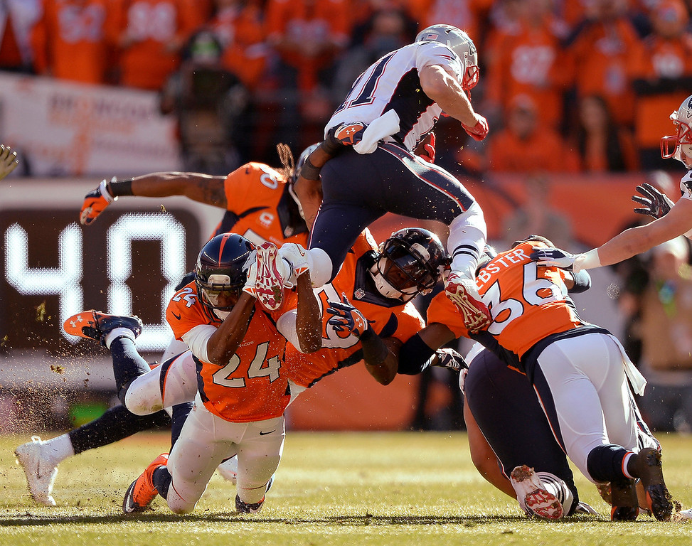 . Denver Broncos cornerback Champ Bailey (24) grabs the foot of New England Patriots wide receiver Julian Edelman (11) as he tries to leap over the Broncos defense during the AFC Championship game at Sports Authority Field at Mile High in Denver on January 19, 2014. (Photo by John Leyba/The Denver Post)