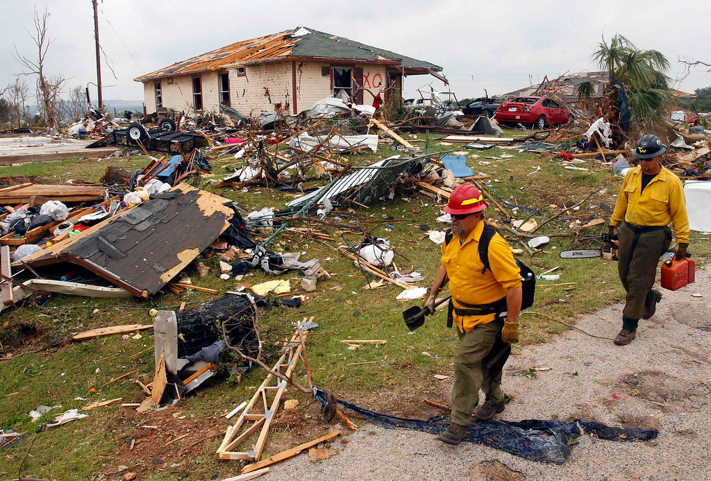 . Rescue workers walk past debris May 16 after tornados swept through the town of Granbury, Texas late May 15, 2013. REUTERS/Richard Rodriguez