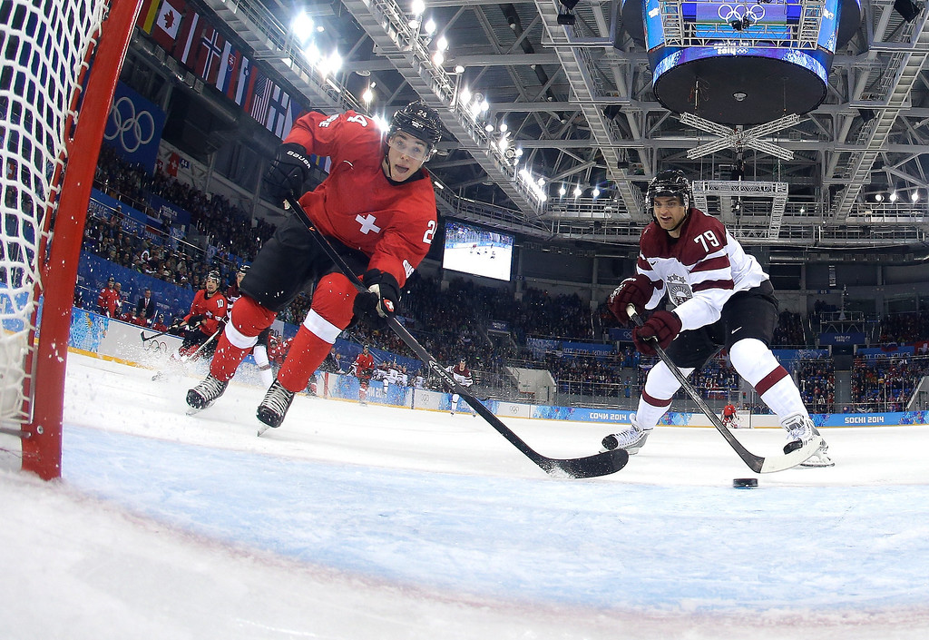 . Reto Suri #24 of Switzerland misses a puck passing in front of an open net against Vitalijs Pavlovs #79 of Latvia in the second period during the Men\'s Ice Hockey Preliminary Round Group C game on day five of the Sochi 2014 Winter Olympics at Shayba Arena on February 12, 2014 in Sochi, Russia.  (Photo by Matt Slocum - Pool/Getty Images)
