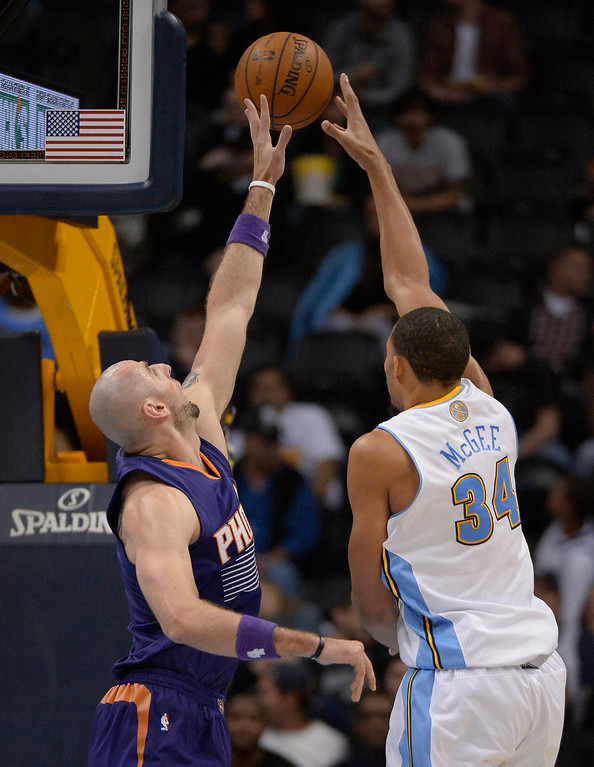 . Denver Nuggets center JaVale McGee (34) just gets a shot off over Phoenix Suns center Marcin Gortat (4) during the fourth quarter October 23, 2013 at Pepsi Center. (Photo By John Leyba/The Denver Post)