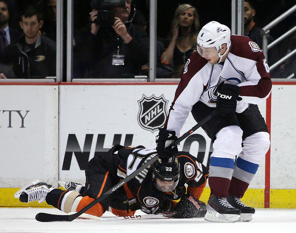 . Anaheim Ducks\' Mathieu Perreault (22) falls to the ice as he fights for the puck with Colorado Avalanche\'s Erik Johnson (6) during the first period of an NHL hockey game Sunday, April 13, 2014, in Anaheim, Calif. (AP Photo/Jae C. Hong)