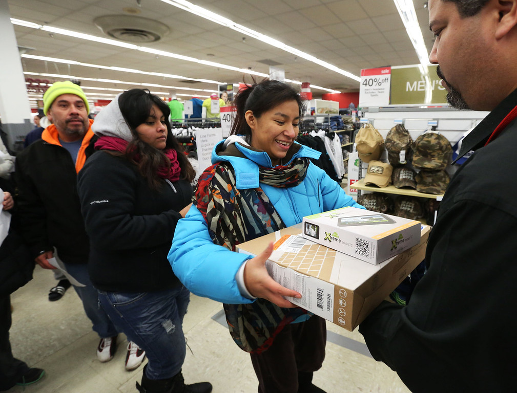 . Rosa Rodriguez, of Chicago, picks up a tablet and a laptop during the doorbuster deals at the Kmart store on Addison St., on Thursday, Nov. 28, 2013 in Chicago, Ill. Rodriguez arrived at 1:30am for the first deals of the season as Kmart was the first major retailer to open it\'s doors for pre-Black Friday shopping on Thanksgiving Day at 6am. (John Konstantaras/AP Images for Kmart)