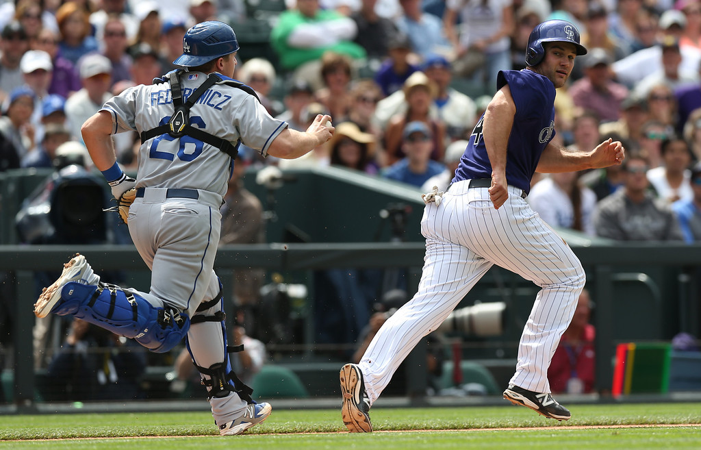 . Los Angeles Dodgers catcher Tim Federowicz, left, runs to tag out Colorado Rockies\' Ryan Wheeler as he tries to return to third base after getting caught in a rundown while trying to advance to home plate on a sacrifice bunt in the fifth inning of a baseball game in Denver on Saturday, June 7, 2014. (AP Photo/David Zalubowski)