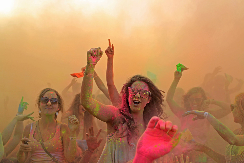 . People react inside a cloud of  paint powder during the holi one colour Festival held in the city of Cape Town , South Africa, Saturday, March 2, 2013. Thousands of people took part in the festival by throwing coloured paint powder at each other to express freedom and the colour of everyday life. (AP Photo/Schalk van Zuydam)