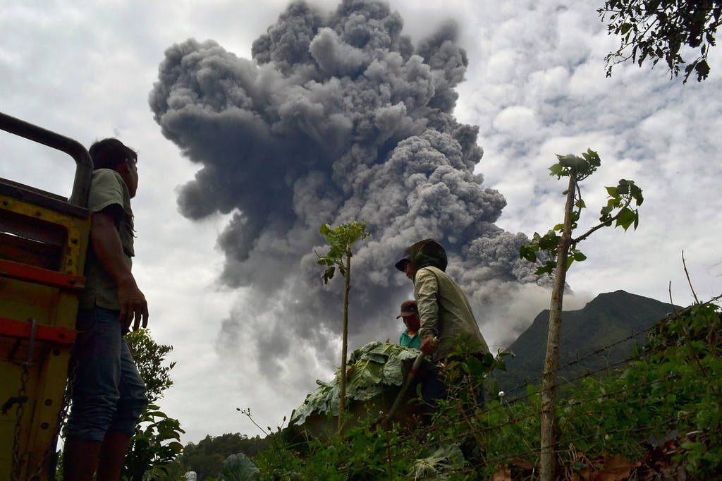 . Indonesian farmers rush to harvest crops in the district of Karo as an ash cloud rises during a fresh eruption of the Mount Sinabung volcano on September 17, 2013. Thousands of villagers fled after Mount Sinabung\'s series of volcanic eruptions on Indonesia\'s Sumatra island, spewing rocks and red-hot ash onto surrounding villages, officials said.   SUTANTA ADITYA/AFP/Getty Images