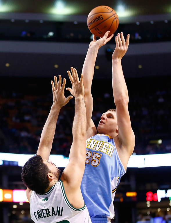 . BOSTON, MA - DECEMBER 06:  Timofey Mozgov #25 of the Denver Nuggets puts up a shot in front of Vitor Faverani #38 of the Boston Celtics in the second half during the game at TD Garden on December 6, 2013 in Boston, Massachusetts.  (Photo by Jared Wickerham/Getty Images)