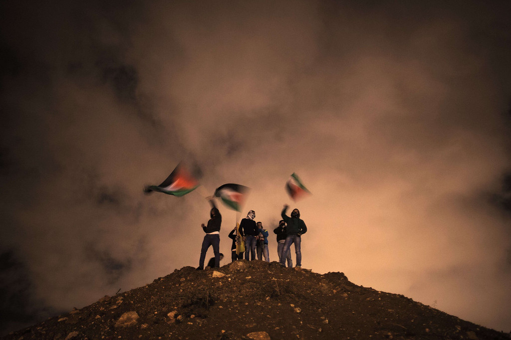 . Palestinians wave their national flag as they await the release of Palestinian prisoners to Jerusalem December 31, 2013.  Israel has freed 26 Palestinian prisoners under peace talks brokered by US Secretary of State John Kerry, who is returning to the region to boost the faltering negotiations.    MENAHEM KAHANA/AFP/Getty Images