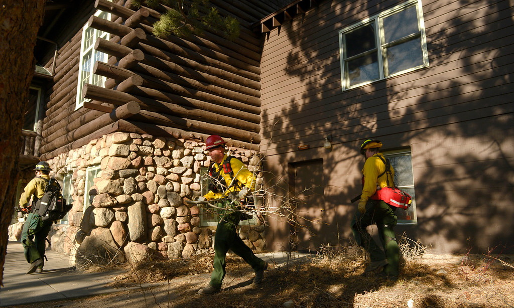 . Wildland firefighters from Lafayette Fire clear brush and debris from the Moraine Park Vistor\'s Center to protect the structure just in case the fire reaches the building on December 2nd, 2012. The Fern Lake Fire, which has been burning in Rocky Mountain National Park since October, kicked up yesterday and forced the evacuation of hundreds of homes east of the fire. Helen H. Richardson, The Denver Post