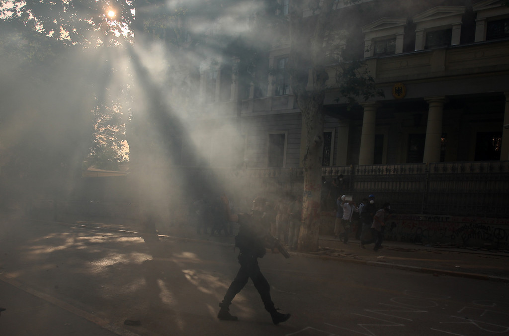 . A policeman is seen through tear gas at the start of an operation to evacuate the Taksim Square in Istanbul Tuesday, June 11, 2013.  (AP Photo/Thanassis Stavrakis)