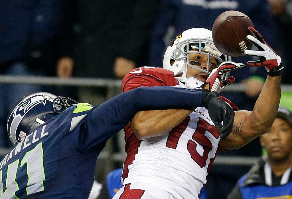 . Arizona Cardinals wide receiver Michael Floyd (15) makes a catch for a touchdown around the defense of Seattle Seahawks cornerback Byron Maxwell, left, in the second half of an NFL football game, Sunday, Dec. 22, 2013, in Seattle. (AP Photo/Elaine Thompson)