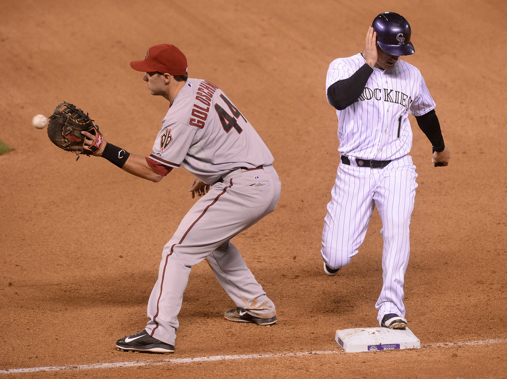 . DENVER, CO - APRIL 5:  Colorado baserunner Brandon Barnes (1) scooted back to the bag on a pick off attempt thrown to Arizona\'s Paul Goldschmidt (44) in the seventh inning. The Colorado Rockies defeated the Arizona Diamondbacks 9-4 Saturday night, April 5, 2014 in Denver. (Photo by Karl Gehring/The Denver Post)
