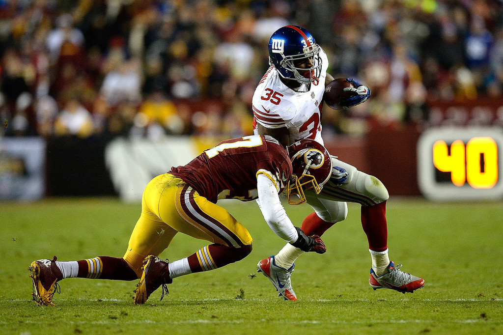 . Andre Brown #35 of the New York Giants is tackled by Reed Doughty #37 of the Washington Redskins in the first half during an NFL game at FedExField on December 1, 2013 in Landover, Maryland.  (Photo by Patrick McDermott/Getty Images)