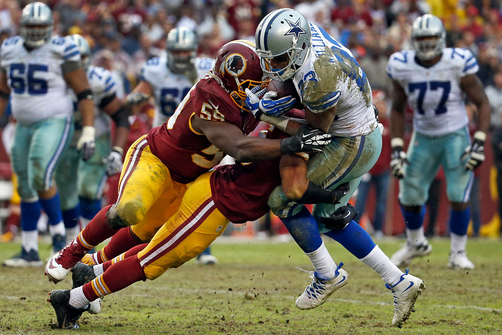. Dallas Cowboys wide receiver Terrance Williams is stopped by Washington Redskins inside linebacker London Fletcher (59) and another defender during the second half of an NFL football game in Landover, Md., Sunday, Dec. 22, 2013. (AP Photo/Alex Brandon)