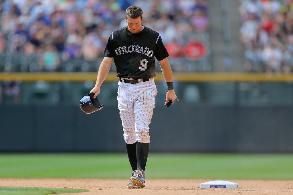 . DJ LeMahieu #9 of the Colorado Rockies walks back to the dugout after getting caught stealing during the sixth inning against the Minnesota Twins at Coors Field on July 13, 2014 in Denver, Colorado. The Twins defeated the Rockies 13-5. (Photo by Justin Edmonds/Getty Images)