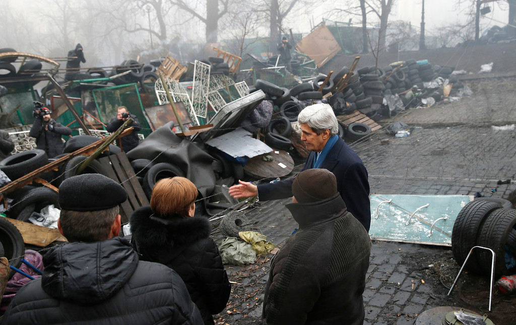 """. Secretary of State John Kerry stands beside a barricade at the Shrine of the Fallen in Kiev,Ukraine, Tuesday, March 4, 2014. The Shrine of the Fallen, located on Institutska Street, honors the fallen Heroes of the \""""Heavenly Sotnya\"""" (Hundred). Over the course of the EuroMaidan protests, almost 100 protesters were killed by police. (AP Photo/Kevin Lamarque, Pool)"""