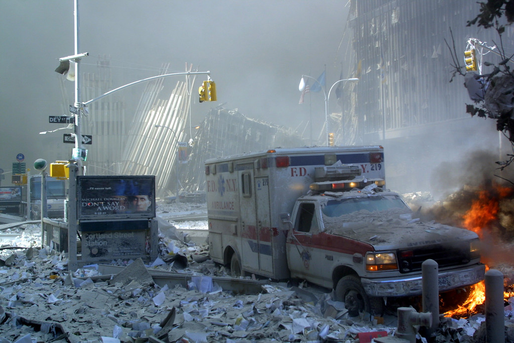 . An ambulance, covered with debris, is on fire after the collapse of the first World Trade Center Tower 11 September, 2001 in New York.  AFP PHOTO  Doug KANTER /AFP/Getty Images