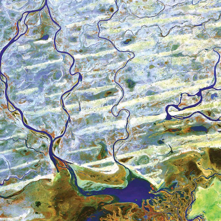 . Niger River, Mali The Niger River and smaller rivers and streams flow northward out of Lake Debo in landlocked Mali in Western Africa. This region is part of the Inner Niger Delta, an intricate combination of lakes, river channels, and swamps with occasional areas of higher elevation. Known as the Macina, this wet oasis in the African Sahel is one of the largest wetlands in the world and provides habitat both for migrating birds and for West African manatees. The fertile floodplains also provide much-needed resources for the local people, who use the area for fishing, grazing livestock, and cultivating rice. This Terra image from 2003 shows the region during the dry season. On the right, water in rivers, streams, and lakes appears blue. On the left, the water turns greener, perhaps because of sediment. The reddish ridges running from east to west in the bottom half of the image are dunes. The pale-gray or white areas between the dunes are flat areas of silt, clay, or sandy soil. Blue shows where water has filled in between some of the dunes.   NASA