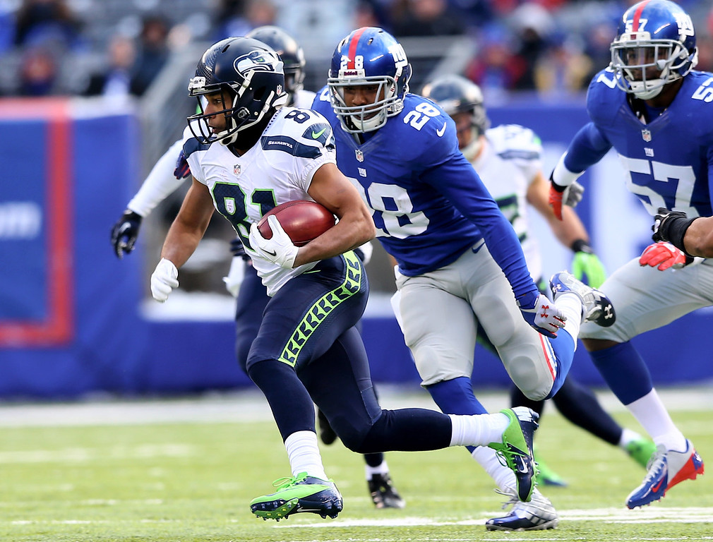 . Golden Tate #81 of the Seattle Seahawks carries the ball as  Jayron Hosley #28 of the New York Giants defends at MetLife Stadium on December 15, 2013 in East Rutherford, New Jersey.  (Photo by Elsa/Getty Images)