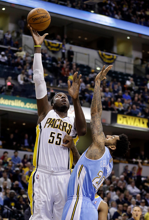 . Indiana Pacers center Roy Hibbert (55) shoots over Denver Nuggets forward Wilson Chandler in the second half of an NBA basketball game in Indianapolis, Monday, Feb. 10, 2014. The Pacers won 119-80.  (AP Photo/Michael Conroy)