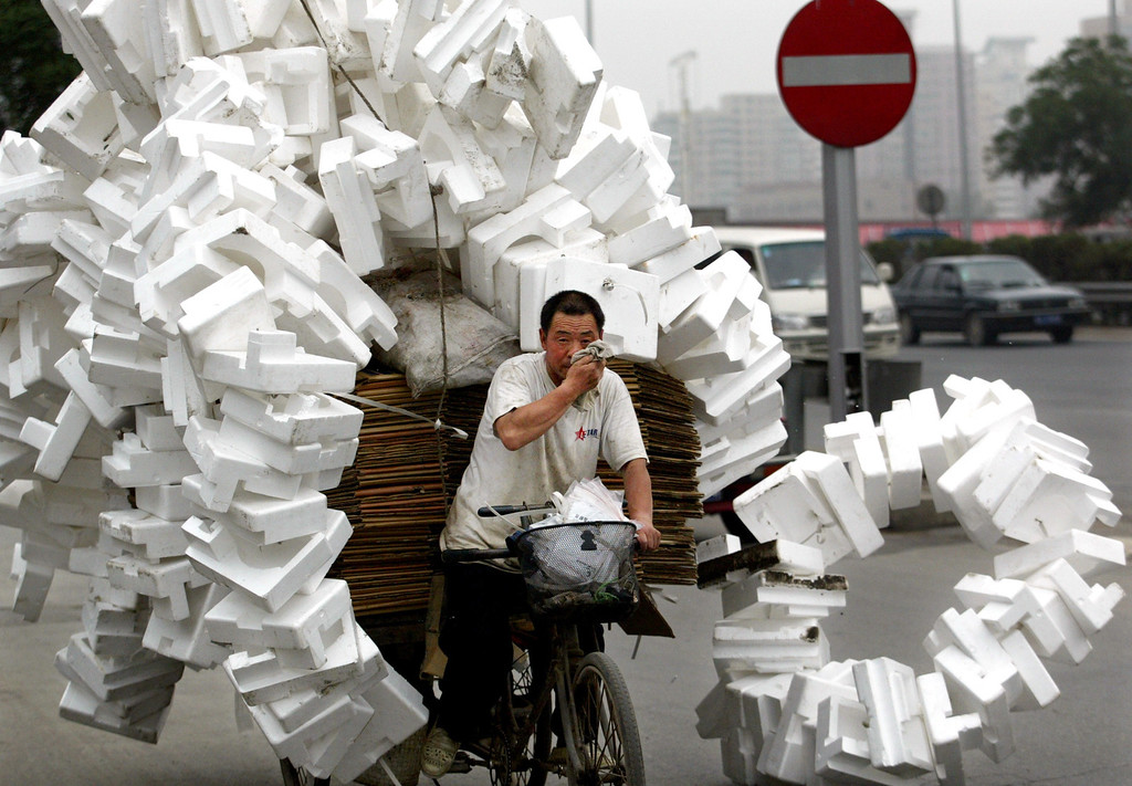 . A Chinese man transfers recyclable rubbish which he collects from streets with a three-wheeled flat-bed bicycle in Beijing June 28, 2002. REUTERS/China Photo