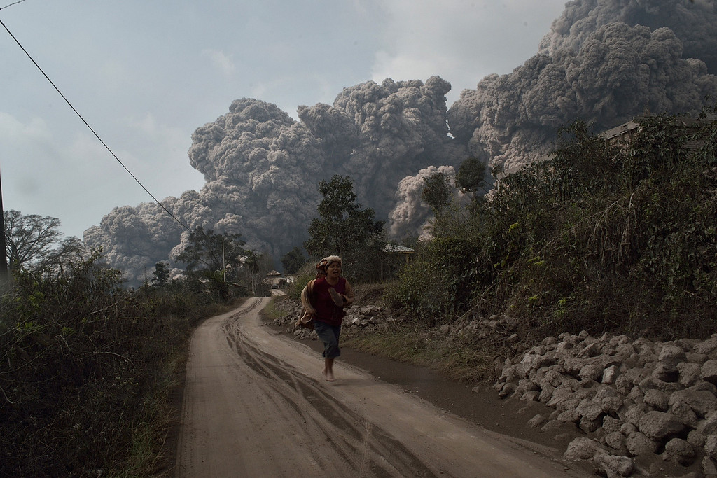 . A resident runs away to escape from hot volcanic ash clouds engulfing villages in Karo district during the eruption of Mount Sinabung volcano located in Indonesia\'s Sumatra island on February 1, 2014.  AFP PHOTO / SUTANTA ADITYA/AFP/Getty Images