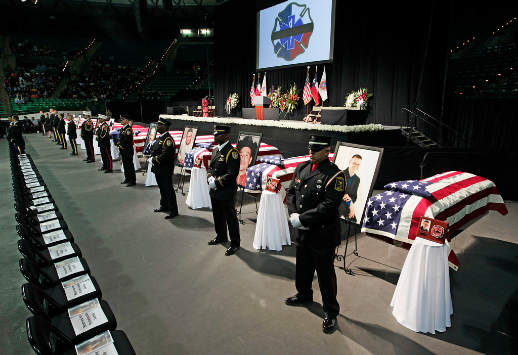 . An honor guards stand next to twelve caskets at the West Memorial Service on April 25, 2013 in Waco, Texas. The memorial service honored the volunteer firefighters that lost their lives at the fertilizer plant explosion in West, Texas last week. (Photo by Erich Schlegel/Getty Images)