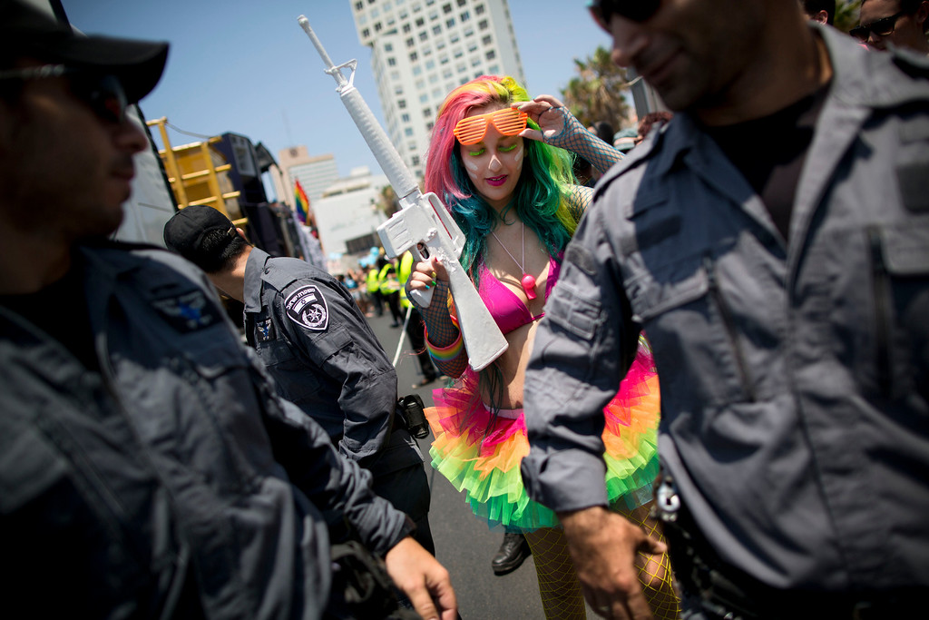 . An Israeli youth with a toy gun walks by police officers during the annual Gay Pride Parade on a street of Tel Aviv, Israel, Friday, June 13, 2014.  (AP Photo/Oded Balilty)